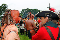 Indian scout wears war paint, feathers in hair, nose and ear rings, at a Revolutionary War reenactment,  Fort Ticonderoga, New York, USA.