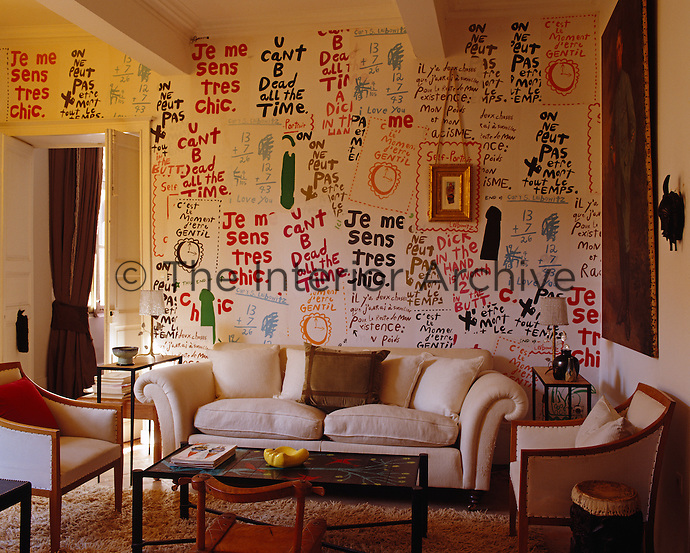 Wallpaper with provocative slogans by American artist Cary Leibowitz breaks down the formality of the living room