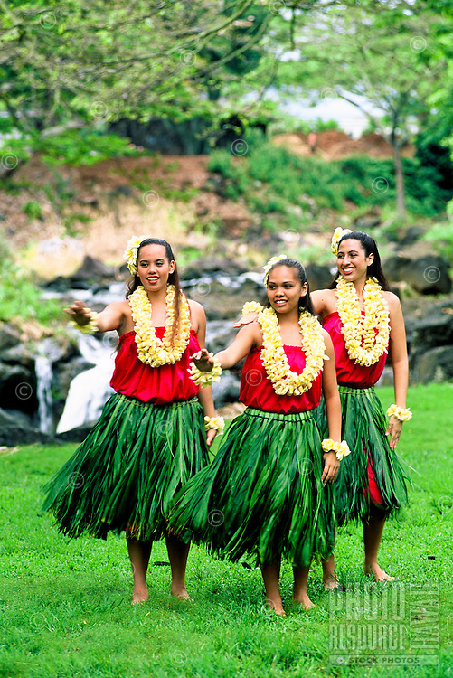 Three hula dancers near Waterfall in ti leaf skirts and yellow plumeria leis