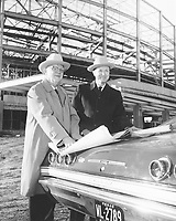 Arlington State College Director of Business and Finance B.C. Barnes and ASC President Dr. Jack R. Woolf review architect's plans for ASC multipurpose auditorium [Texas Hall] construction on hood of car, ca. 1965