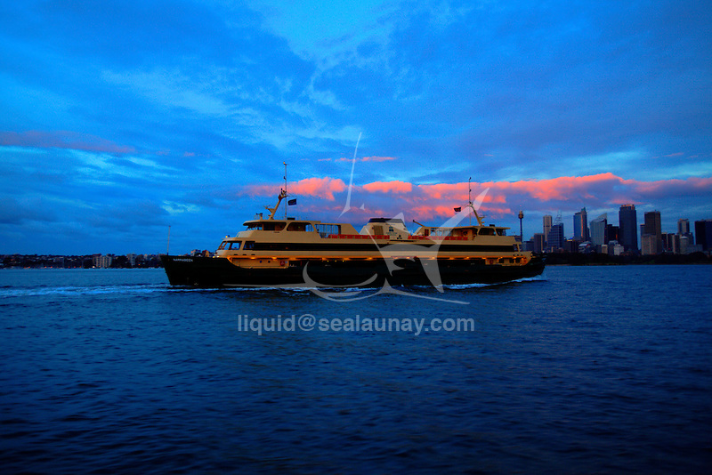 A Sydney Ferry on this way to the city of Sydney early in the morning under a cloudy sunrise.
