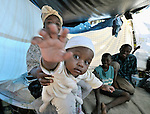 Survivors of the devastating January 12 earthquake gather inside their makeshift shelter in a camp for homeless families in Port-au-Prince, Haiti.