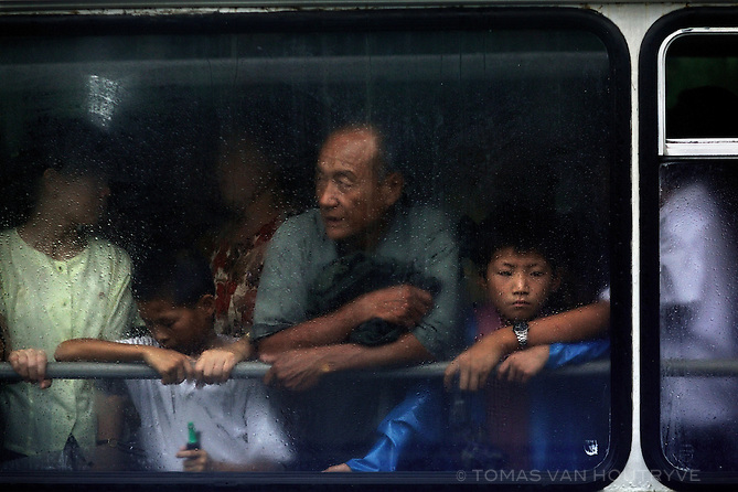 Passengers look out froma bus window in the rain in Pyongyang, North Korea (DPRK) on 14 August, 2007.