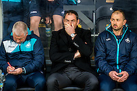 ( L-R ) Swansea City Assistant manager, Nigel Gibbs,  Manager of Swansea City Paul Clement and Swansea City and Swansea Fitness coach, Karl Halabi sit in the dugout  ahead of the Emirates FA Cup Third Round match between Hull City v Swansea City at KCOM Stadium, Hull, England, UK. Saturday 07 January 2017