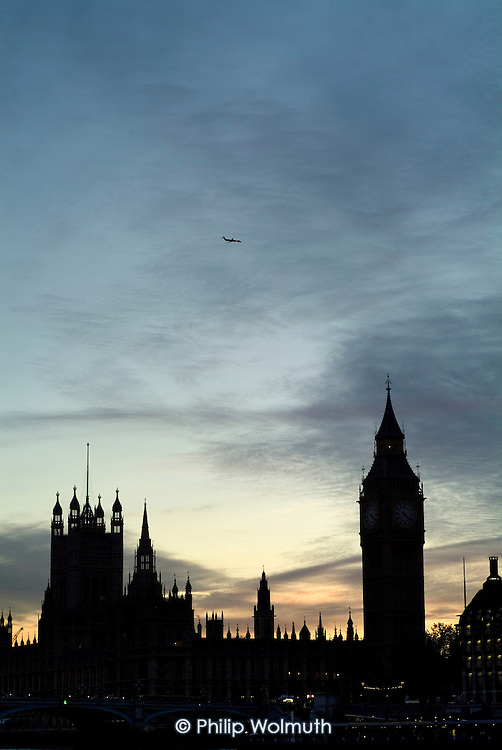 An aeroplane passes over Big Ben and the Houses of Parliament
