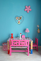 The table and bench seat in this child's room have been covered with a flowered plastic tablecloth from 'Kitsch Kitchen'
