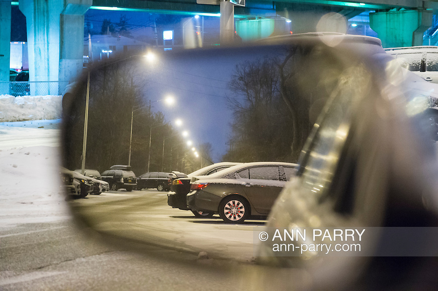 Merrick, New York, USA. March 3, 2015. During peak of evening commute, snow falls at Merrick Long Island Rail Road LIRR train station parking lot, as seen in side view mirror of car. The area is under a Winter Weather Advisory, and a Winter Storm Watch for hazardous conditions is in effect from Wednesday night to Thursday night in Long Island, New York City and other nearby areas of the northeast.
