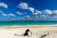 A couple embraces on the shore in Playa del Carmen, Mexico.