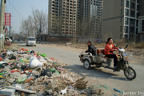 People drive past garbage left outside a building site in Hebei, on the outskirts of Beijing, where rural land is increasingly destroyed to make way for urbanisation. <br /> <br /> China is pushing ahead with a dramatic, history-making plan to move 100 million rural residents into towns and cities over six years &mdash; but without a clear idea of how to pay for the gargantuan undertaking or whether the farmers involved want to move.<br /> <br /> Moving farmers to urban areas is touted as a way of changing China&rsquo;s economic structure, with growth based on domestic demand for products instead of exporting them. In theory, new urbanites mean vast new opportunities for construction firms, public transportation, utilities and appliance makers, and a break from the cycle of farmers consuming only what they produce.<br /> <br /> Urbanization has already proven to be one of the most wrenching changes in China&rsquo;s 35 years of economic reforms. Land disputes rising from urbanization account for tens of thousands of protests each year.