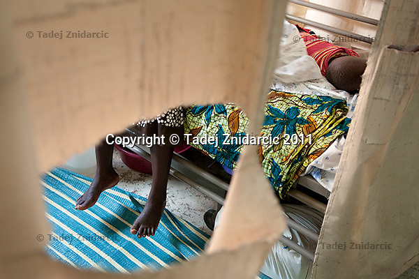 Expecting mother sits on the bed in the labor ward of Arua Hospital, Uganda.