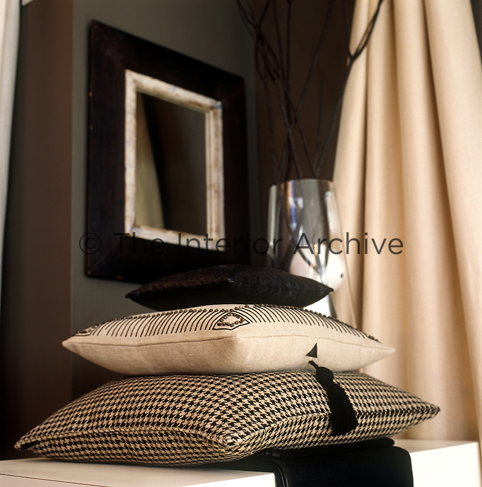 In the living room is a pile of cushions either embroidered, tasselled or in houndstooth check