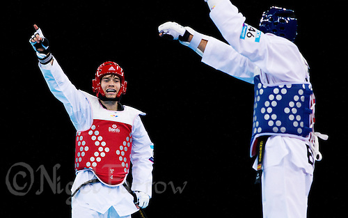 04 DEC 2011 - LONDON, GBR - Aaron Cook (GBR) (on left, in red) and Nicolas Garcia (ESP) (on right, in blue) both tries to claim points during their men's -80kg category semi final contest at the London International Taekwondo Invitational and 2012 Olympic Games test event at the ExCel Exhibition Centre in London, Great Britain .(PHOTO (C) NIGEL FARROW)