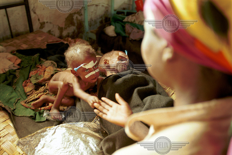 © J.B. Russell / Panos Pictures..Bailundo, Angola. 01/08/2002...A mother with her severely malnurished children at a Medecins Sans Frontieres (MSF) therapeutic feeding centre. The military strategies of the government armed forces and UNITA rebels toward the civilian population has caused widespread devastation and a serious famine situation in the country. Aid organizations have had access to large portions of the country only after a cease fire was signed in April of this year.