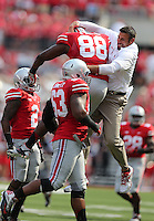 OSU defensive coach Mike Vrable jumps with Ohio State Buckeyes defensive lineman Steve Miller (88) after miller sacked San Diego's quarterback in the first quarter of a football game between the Ohio State Buckeyes and the San Diego State Aztecs on Sept. 7, 2013 at Ohio Stadium. (Columbus Dispatch photo by Fred Squillante)