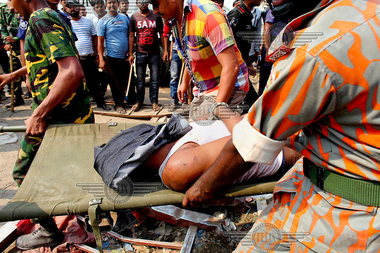 A man is pulled out of the rubble of the collapsed Rana Plaza complex in Savar on the outskirts of Dhaka by rescuers and army personnel. The 8 storey Rana Plaza complex, which housed a number of garment factories employing over 3,000 workers, collapsed on 24 April 2013. By 29 April, at least 380 were known to have died while hundreds remained missing. Workers who were worried about going to work in the building when they noticed cracks in the walls were told not to worry by the building's owner, Mohammed Sohel Rana, who is a member of the ruling Awami League's youth front. He fled his home and tried to escape to neighbouring India after the building collapsed but was caught by police and brought back to Dhaka. Some of the factories working in the Rana Plaza building produce cheap clothes for various European retailers including Primark in the UK and Mango, a Spanish label. The final death toll was 1,127. /Felix Features