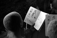 Mozambico, distretto di Chure. Bambini a scuola elementare. Libro abecedario