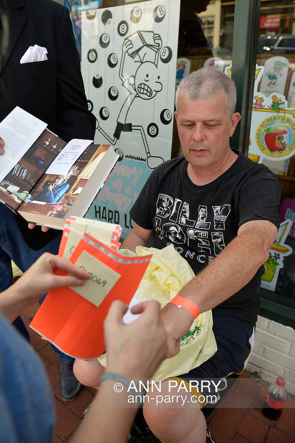 Huntington, New York, U.S. - August 6, 2014 - KENNY MITCHELL, of Garden City, has been waiting on line over 15 hours, since 11:10 pm the night before, to be the first on line to attend the book signing for H. Clinton's new memoir, Hard Choices, at the Book Revue in Huntington, Long Island. Clinton's book is about her four years as America's 67th Secretary of State and how they influence her view of the future. People on line had to show their book and receipt from Book Revue in order to get an orange wrist band and a number for their book to be signed.