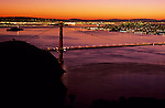 Golden Gate Bridge at sunrise with city lights and San Francisco Bay illuminated from Marin Hills looking out over San Francisco, California USA  The Golden Gate connects San Francisco penninsula and Marin penninsula and is nearly two miles long,  San Francisco, California USA