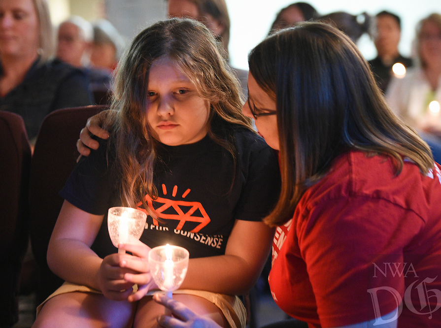 "NWA Democrat-Gazette/CHARLIE KAIJO Amy Gillespie of Bella Vista (right) comforts her daughter Evie Gillespie, 10, during a vigil, Thursday, August 8, 2019 at the All Saints' Episcopal Church in Bentonville.<br /> <br /> Moms Demand Action of Benton County held a candle light vigil to honor the victims of the El Paso, TX. and Dayton, OH. shootings that took the lives of 31 people. About 120 people attended the vigil. Attendees listened to impassioned speakers and participated in a moment of silence and prayer. Afterwards, organizers handed out postcards to mail to Arkansas Senators Tom Cotton and John Boozeman and Kentucky Senator Mitch McConnel urging them to support House Resolution 8 which would require backgrounds checks on all gun sales or transfers. <br /> <br /> Brandi Gonzalez, a former El Paso resident of six years, brought her two children to the vigil wearing matching ""El Paso Strong"" t-shirts. ""Shock,"" she said of her reaction to hearing the news. ""I worked across the street from the Walmart. That's where we went shopping. My kids are Mexican American. I don't want them to feel ashamed for who they are and where they come from or what their background is."""