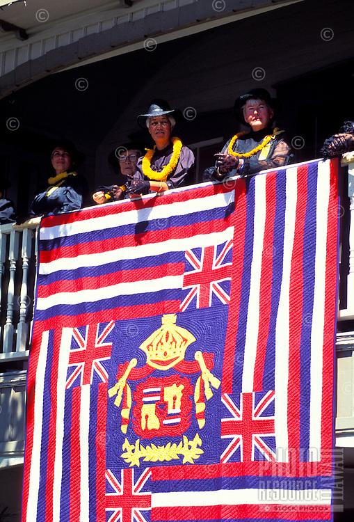 Aloha Festival with Aunties watching above the  Hawaiian flag quilt on display, Waimea, Big island of Hawaii