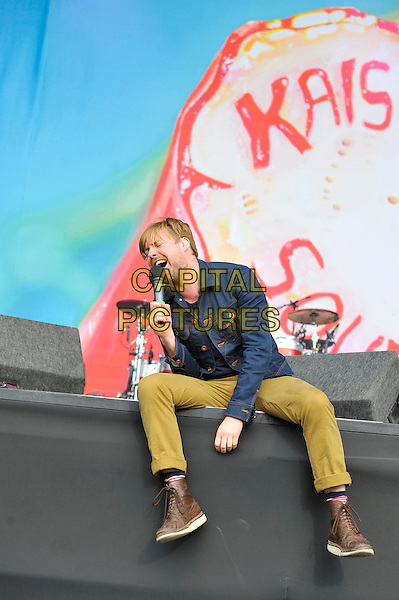Ricky Wilson of Kaiser Chiefs.performing on Day 3 at Reading Festival, Reading, England. .26th August 2012.on stage in concert live gig performance performing music full length blue  jacket khaki trousers singing beard facial hair sitting .CAP/MAR.© Martin Harris/Capital Pictures.