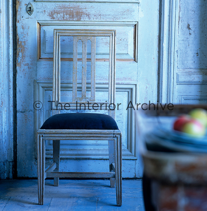 Detail of a wooden chair in front of a distressed wooden door with a bowl of fruit on a tray table in the foreground
