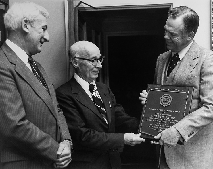 Executive vice president of retired officers association Colonel Donald foster (right) congratulates Rep. Charles Melvin Price, D-Ill., for his devoted service to the military community as Colonel George Hennrikus, Chief legislative counsel looks on. Jan. 18, 1979. (Photo by CQ Roll Call)