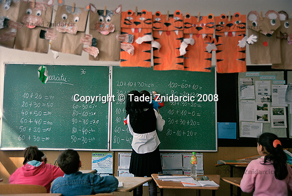 Teacher helps a small boy solve a math problem on the blackboard in an after-school program, organized by Ovidiu Rom. Bacau, Romania.