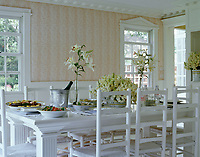 A summer dining room furnished with white chairs and a table laid for an impromptu lunch