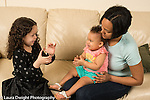 10 month old baby girl held by mother playing clapping game with 6 year old girl