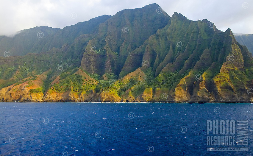 The Na Pali coast of Kauai is alight with the setting sun as seen from a cruise ship.