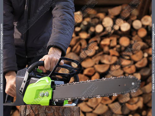 CLoseup of hands of a man holding an Electric Cordless chainsaw in front of stacked firewood in the background