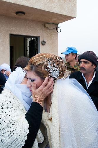 Plateau du Golan, dans la zone tampon entre la Syrie et Israel, Jan 2011. Dans le cadre de la reunification familiale facilitee par le CICR (Comite International de la Croix Rouge), un mariage a lieu entre une Syrienne et un  Israelien de la comunaute druze, qui est separee des deux cotes de la frontiere. Samar, la mariee, dit adieu a sa mere: elle ne sait pas quand elle aura l'occasion de la revoir, car elle ne pourra pas repasser la frontiere. Le temps d'une petite heure, c'est une occasion unique de revoir des parents qui vivent de l'autre cote de la frontiere depuis qu'Israel a annexe le Golan en 1981 (annexion non reconnue a ce jour par l'ONU). Seul le CICR est habilite a coordoner ce genre de reunion, car la frontiere est fermee pour les civils.