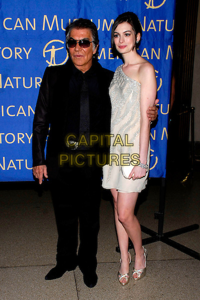 ROBERTO CAVALLI & ANNE HATHAWAY.Roberto Cavalli sponsors the American Museum of Natural History's annual Winter Dance held at the museum, New York, New York, USA..March 11th, 2008.full length black suit sunglasses shades white cream silver one shoulder dress clutch bag purse.CAP/ADM/BL.©Bill Lyons/AdMedia/Capital Pictures.