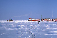 After building a snow bridge to disperse weight, housing and equipment trailers are towed safely over a crack in the sea ice. Geophysical crews work during the arctic winter when they can travel out onto the ice of the Beafort Sea, north of the coast of Alaska. Photo taken in 1980 of a D7 Caterpillar tractor moving trailers, which are on Ski's.