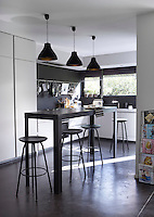 The contemporary monochrome kitchen features a polished iron table and bar stools