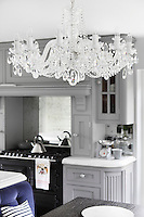 A traditional crystal chandelier hangs from the kitchen ceiling