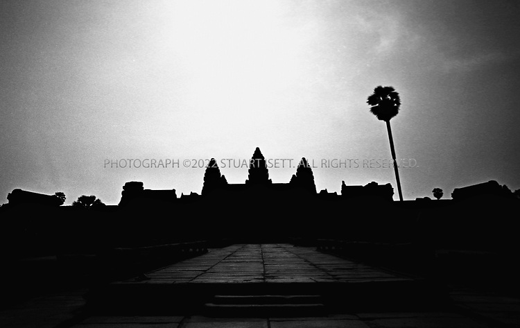 """4/20/2003--Angkor Wat Temples, Siem Reap, Cambodia..Sunrises over Angkor Wat. Angkor Wat is located about six kilometers (four miles) north of Siem Reap, south of Angkor Thom. ..Angkor Wat was built in the first half of the 12th century (113-5BC). Estimated construction time of the temple is 30 years by King Suryavarman II, dedicated to Vishnu (Hindu), replica of Angkor Thom style of art...BACKGROUND .Angkor Wat, the largest monument of the Angkor group and the best preserved, is an architectural masterpiece. Its perfection in composition, balance, proportions, relief's and sculpture make it one of the finest monuments in the world. ..Wat is the Thai name for temple (the French spelling is """"vat """"), which was probably added to """"Angkor """"when it became a Theravada Buddhist monument, most likely in the sixteenth century (for the etymology of the name 'Angkor' see page 17) After 1432 when the capital moved to Phnom Penh, Angkor Wat was cared for by Buddhist monks. ..It is generally accepted that Angkor Wat was a funerary temple for King Suryavarman II and oriented to the west to conform to the symbolism between the setting sun and death. The bas-reliefs, designed for viewing from left to right in the order of Hindu funereal ritual, support this function. ...All photographs ©2003 Stuart Isett.All rights reserved."""