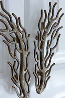 The metal handles of the double doors have been forged in the shape of branched coral