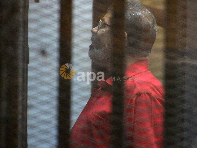 Ousted Egyptian president Mohammed Morsi speaks to the judge as he stands behind bars during his trail in a court in Cairo on August 30, 2015. Cairo criminal court resumes today the trial of deposed president Mohamed Morsi and 10 others on charges of espionage and leaking classified documents related to the national security and the army to Qatar. Photo by Amr Sayed