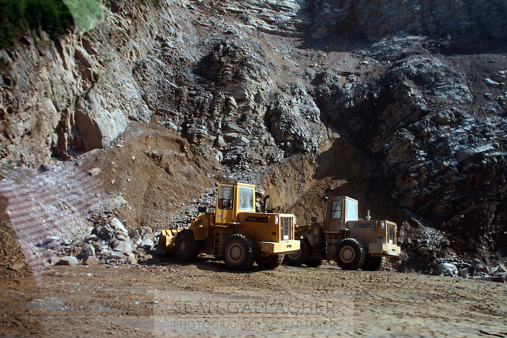 Construction vehicles near a mountainside that has been used to excavate materials for building projects. Sichuan Province.