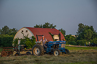 Farmer rakes a dried hay field before baling late on a hot summer day Braun Farm in Westerville, Ohio.