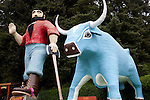 A little boy sits atop Paul Bunyan's foot as Babe the Blue Ox stands by at the entrance of Trees of Mystery, a redwood trail, gondola ride and tourist attraction in Klamath, California.