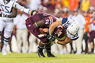 Landover, MD - SEPT 3, 2017: West Virginia Mountaineers offensive lineman Colton McKivitz (53) tackles Virginia Tech Hokies defensive end Trevon Hill (94) following an interception during game between West Virginia and Virginia Tech at FedEx Field in Landover, MD. (Photo by Phil Peters/Media Images International)