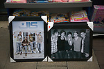 Boy band posters for sale on pavement of discount shop