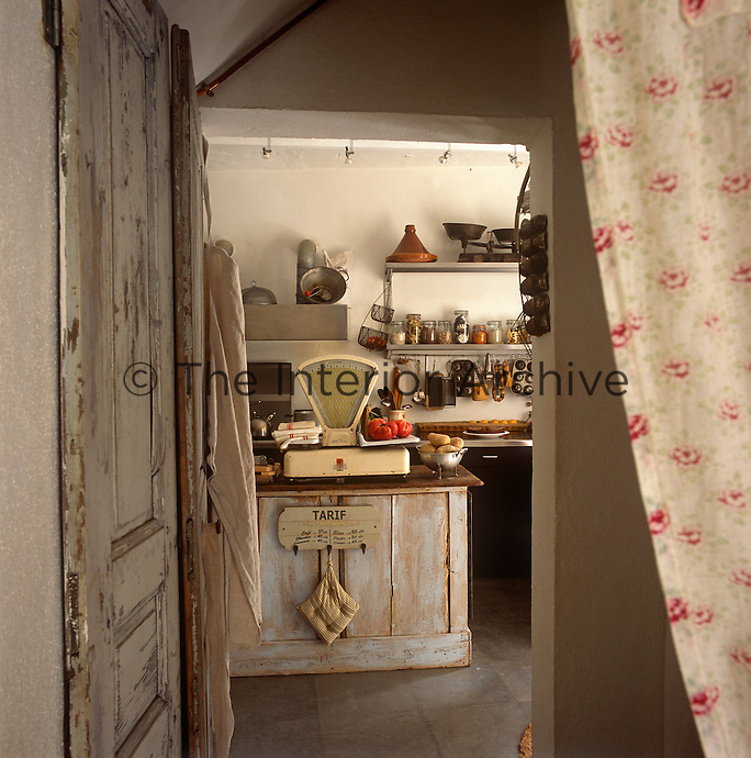 A view through an open doorway to a rustic kitchen with a tiled floor. A traditonal weighing scale is set on a worktop.