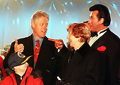 United States President Bill Clinton and Wayne Newton enjoy a private moment as they sang Christmas Carols following the lighting of the 1999 National Christmas Tree on December 9, 1999.  Also in the photo are Fred Sanger, a boy who met Clinton in the White House on Monday courtesy of the Make a Wish Foundation, which helps terminally ill youngsters live their dreams (right) and an unidentifird woman (left)..Credit: Ron Sachs / CNP