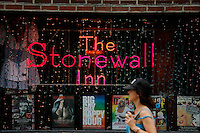 A woman walks in front of the Stonewall Inn bar in New York. 25.06.2015. The Stonewall Inn, the birthplaces of the modern gay rights movement, the Greenwich Village bar for the LGBT community was made a New York City landmark on Tuesday,  Eduardo MunozAlvarez/VIEWpress.