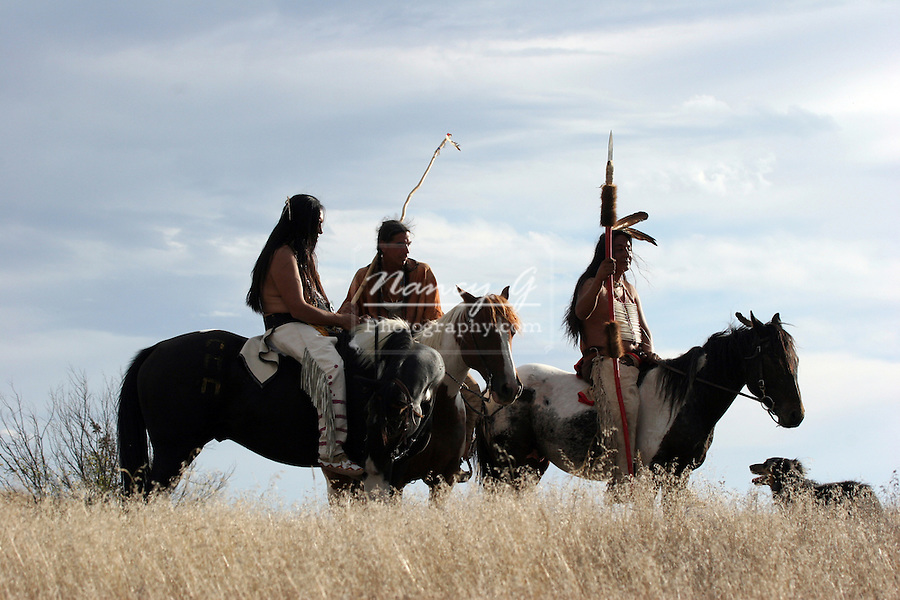 Three Native American Indians on horseback with a dog on the prairie of South Dakota