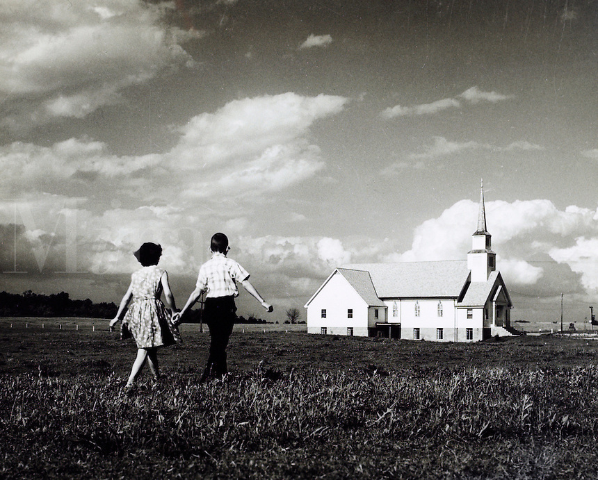 Boy and girl walking across field toward church. 1950's.<br />
